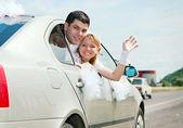 Happy wedding couple in car — Stock Photo