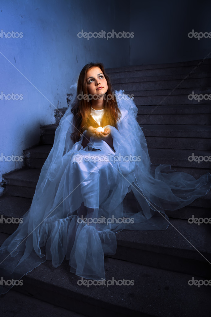Angel with a candle sitting on the stairs  — Stock Photo #7314955