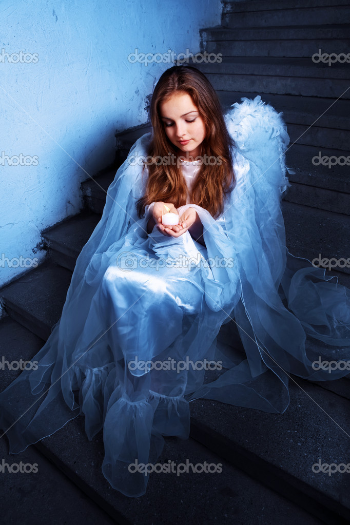Portrait of an angel with a candle sitting on the stairs — Stock Photo #7314958