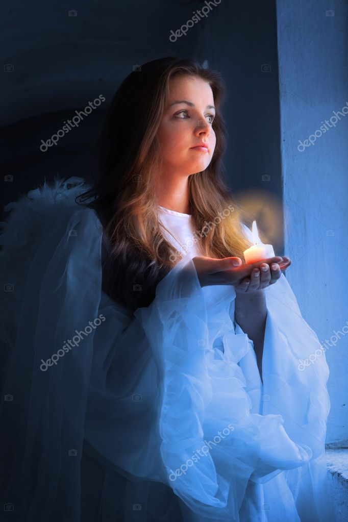 Portrait of an angel with a candle standing near the window. — Stock Photo #7314962