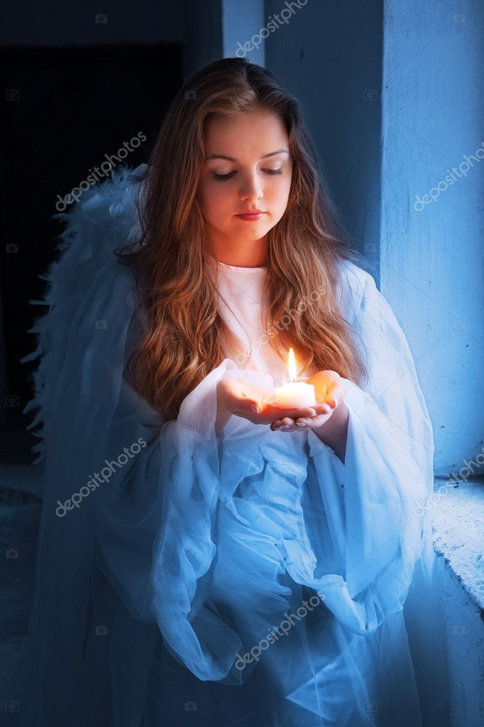 Portrait of an angel with a candle standing near the window.  Stock Photo #7314963