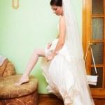 Beautiful bride's leg with white garter — Stock Photo