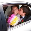 Closeup of newlywed couple kissing in wedding car - Stock Photo