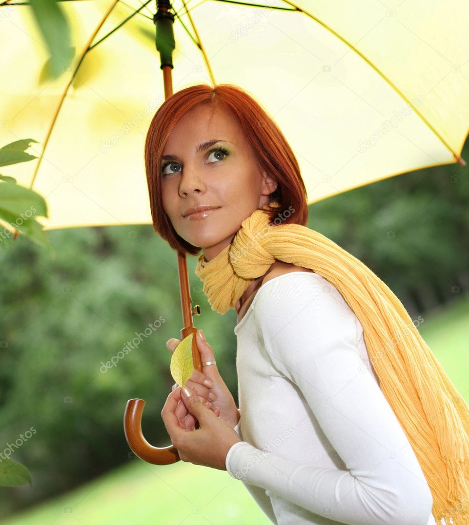 Beautiful girl relaxing on grass under yellow umbrella  Stock Photo #6775649