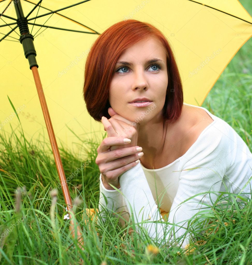 Beautiful girl relaxing on grass under yellow umbrella — Stock Photo #6775651
