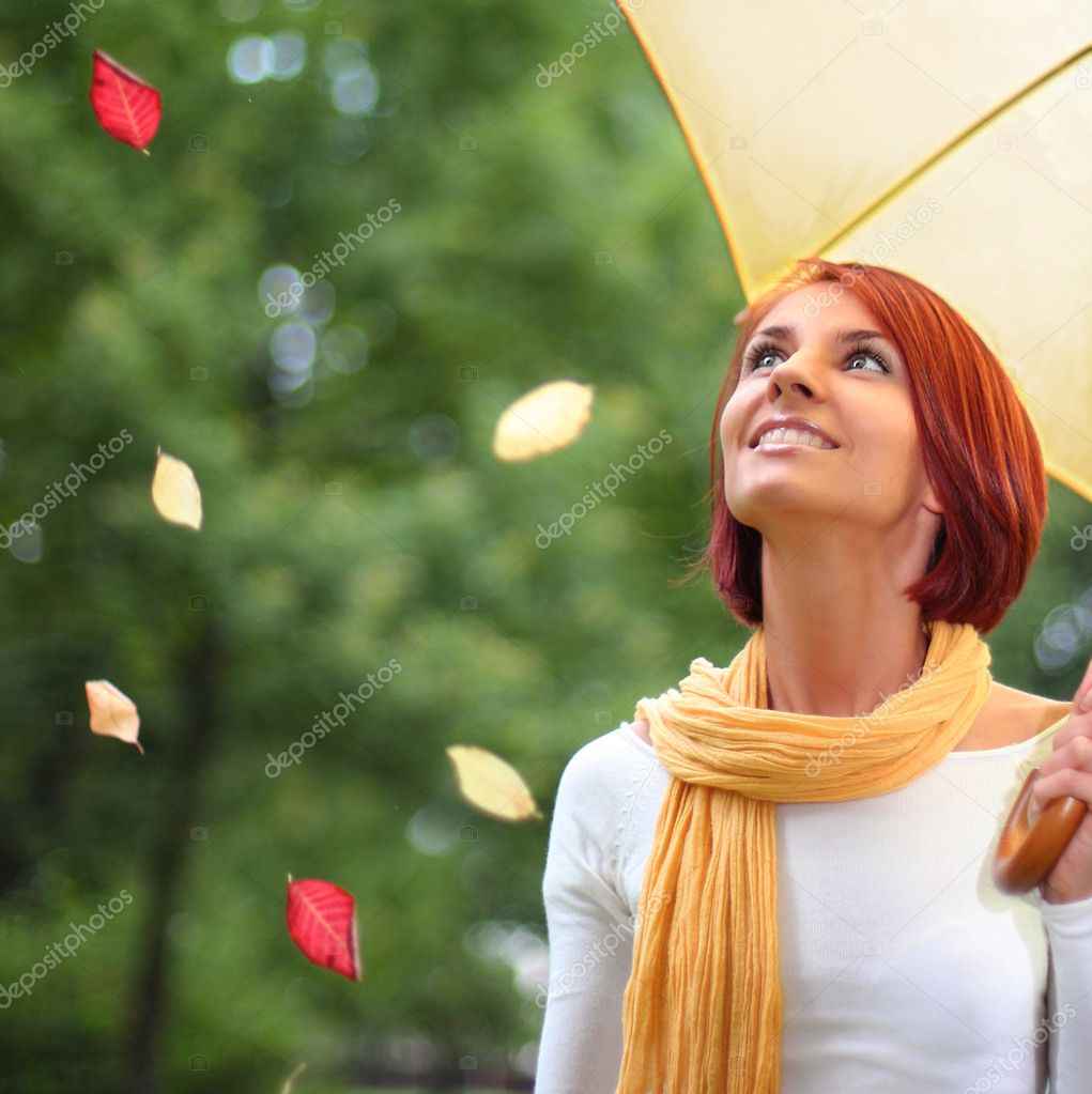 Beautiful girl relaxing on grass under yellow umbrella — Stock Photo #6775658