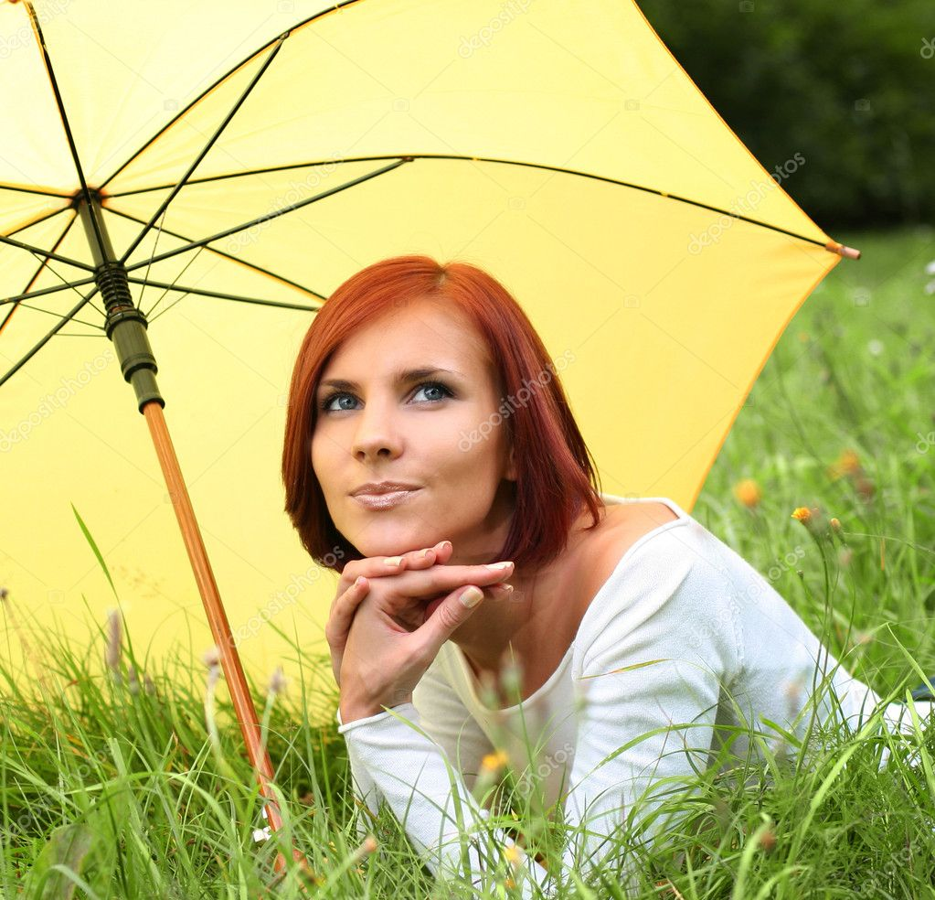 Beautiful girl relaxing on grass under yellow umbrella — Stock Photo #6775668