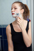 Girl shaving in bathroom — Stock Photo