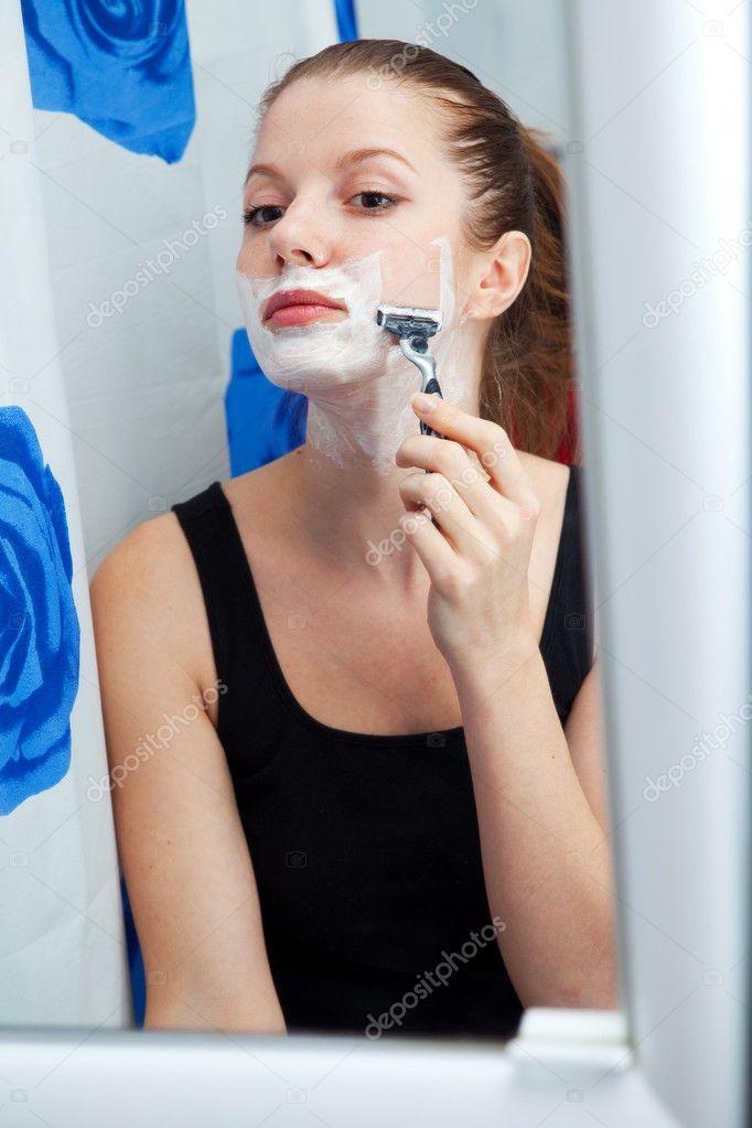 Girl shaving in bathroom stock image