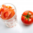 Tomato and slices in glass isolated on white background — Stock Photo