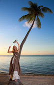 The young beautiful woman with a rose on a palm tree on seacoast — Stock Photo