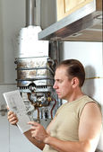 The man with a wrench thinks of repair of a gas water heater — Stock Photo