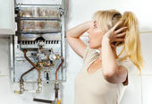 The young woman is upset by that the gas water heater has broken — Stock Photo