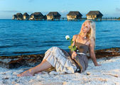 The young woman in a long sundress on a tropical beach. — Stock Photo