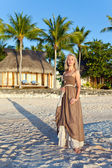 The young woman in a long sundress on a tropical beach. Polynesia. Island T — Stock Photo
