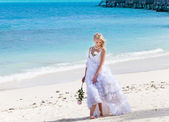 The young beautiful woman in a dress of the bride standing at sea edge — Stock Photo