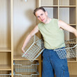 The man establishes baskets in a new wardrobe - Stockfoto