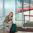 The girl with a road backpack in a station waiting room - Stock Photo