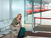 The girl with a road backpack in a station waiting room — Stock Photo