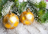 New Year's balls and snow-covered branches of a Christmas tree — ストック写真