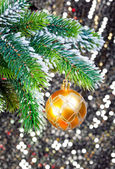 Yellow New Year's balls and snow-covered branches of a Christmas tree — Stockfoto