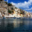 Greece. Dodecanesse. Island Symi (Simi). Colorful houses on rocks. - Stock Photo