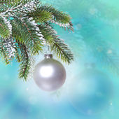 Glass New Year's ball and snow-covered branches of a Christmas tree — Stock Photo