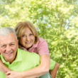 Happy senior man giving piggyback ride mature woman — Stock Photo
