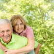 Stock Photo: Happy senior man giving piggyback ride mature woman