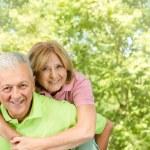 Happy senior man giving piggyback ride mature woman — Stock Photo
