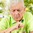 Portrait of worried elderly man playing chess outdoors — Stock Photo #6844934