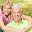 Stock Photo: Happy mature woman embracing elderly man