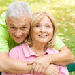 Happy elderly man embracing mature woman - Stockfoto