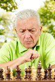Portrait of worried elderly man playing chess outdoors — Stock Photo