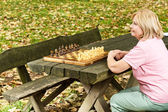 Lonely mature woman sitting on a park bench — Stock Photo