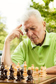 Elderly man thinking about next moves in chess — Stock Photo