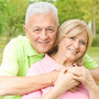Happy elderly man embracing mature woman - Stock Photo