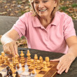 Smiling senior woman playing chess — Stock Photo
