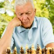 Portrait of worried elderly man playing chess outdoors - Stock Photo