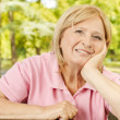 Stock Photo: Portrait of smiling senior woman in the park