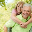 Happy senior man giving piggyback ride — Stock Photo #7009490