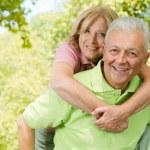Happy senior man giving piggyback ride — Stock Photo