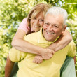 Happy senior man giving piggyback ride — Stock Photo