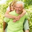 Stock Photo: Happy senior man giving piggyback ride