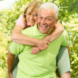 Happy senior man giving piggyback ride — Stock Photo #7009551