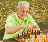 Elderly man playing chess in the park — Stock Photo