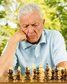 Portrait of worried elderly man playing chess outdoors — Stok fotoğraf