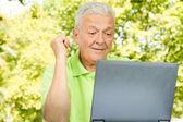 Senior man met laptop buiten — Stockfoto