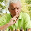 Portrait of worried elderly man playing chess outdoors — Stock Photo #7553370