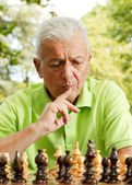 Portrait of worried elderly man playing chess outdoors — Foto Stock